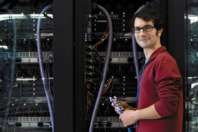 man standing next to server farm